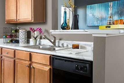 The fully-equipped open-concept kitchen looks out onto the rest of the Fitzsimons South apartment home.
