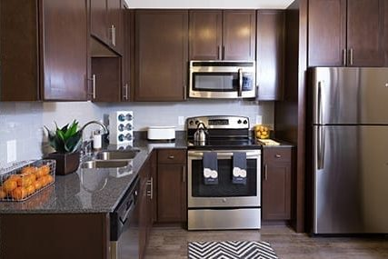 apartment kitchen area with wood floors and matching dark brown wood cabinets, granite countertops and modern stainless steel appliances