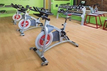 a row of cycling bikes in silver with red accents on a light wood floor facing with a wall mirror facing bikes