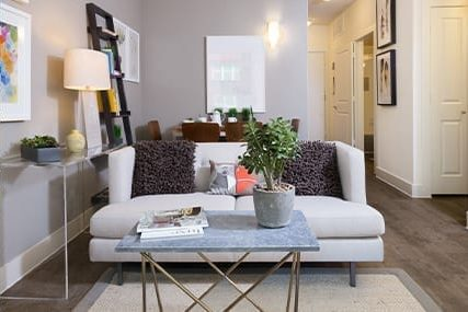 apartment living area decorated with a plush cream couch and stone and gold coffee table on hardwood floors decorated with a grey and white rug